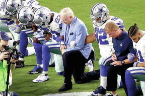The Dallas Cowboys, led by owner Jerry Jones, center, take a knee prior to the national anthem prior to Monday night's game against the Arizona Cardinals, in Glendale, Ariz.