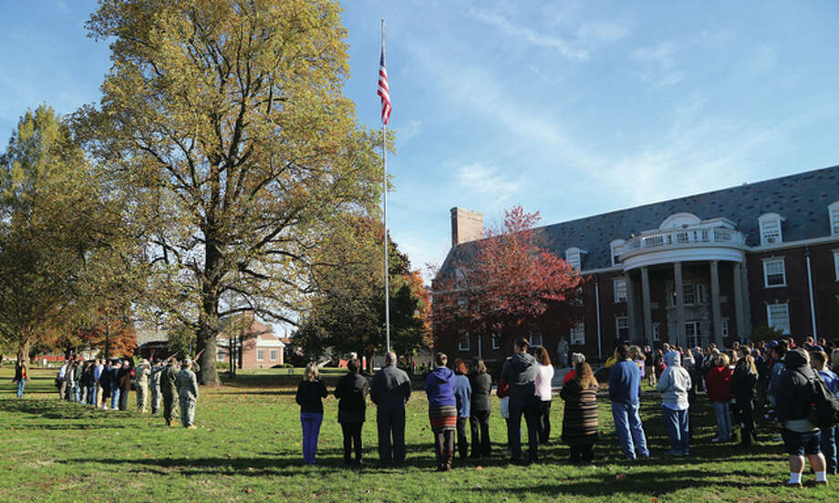 MacMurray College students and faculty and staff members, along with members from the American Legion and AMVETS Post 100, gather Friday on Rutledge Lawn in honor of Veterans Day. Eric Swenson, director of external relations at MacMurray and an Army veteran, began the event by speaking on the history and importance of Veterans Day. Photo: Photo Submitted