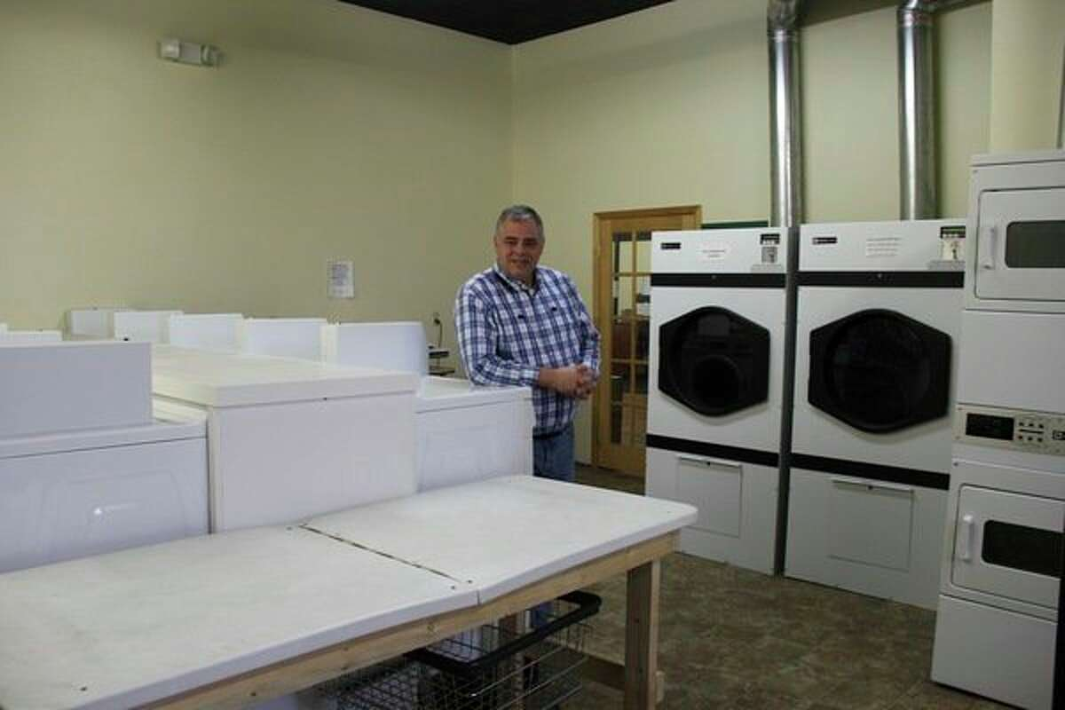 Dean Avola, owner of Green Clean Beans, stands near the laundromat that he has inside his business in downtown Bad Axe. (Chip Burch/Huron Daily Tribune)