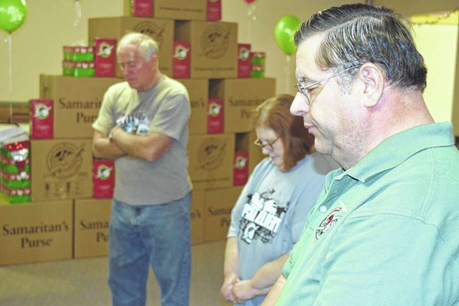 Wayne Ervin, Diane Moody and relay center coordinator Fred Moody pray for donations at the start of collections for this year's Operation Christmas Child. The program collects shoeboxes filled with school supplies, hygiene items, notes of encouragement and toys to be distributed with other collections to 12 million needy children each year. Donations can be dropped off this week at Calvary Baptist Church, 859 N. Main St., from 4 to 7 p.m. weekdays, from 10 a.m. to 2 p.m. Saturday and from 1 to 4 p.m. Sunday. Final collections will be accepted from 9 to 11 a.m. Monday.