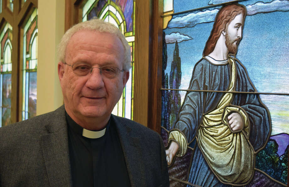 Retiring Salem Lutheran Church Pastor Peter Brechbuhl stands in front of the church's stained glass window that depicts Jesus Christ as the sower. Photo: Greg Olson | Journal-Courier