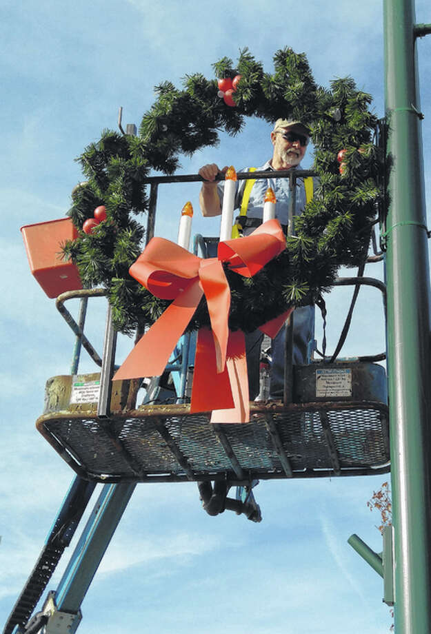 Jacksonville city employee Terry Surratt puts up one of Christmas wreaths Thursday that will adorn the city during the holiday season. Photo: Nick Draper | Journal-Courier