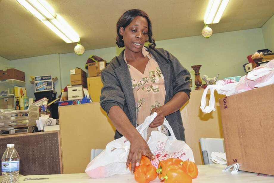 Volunteer Donna Wilkins bags donated food Friday at the New Directions Warming and Cooling Center. Photo: Nick Draper | Journal-Courier