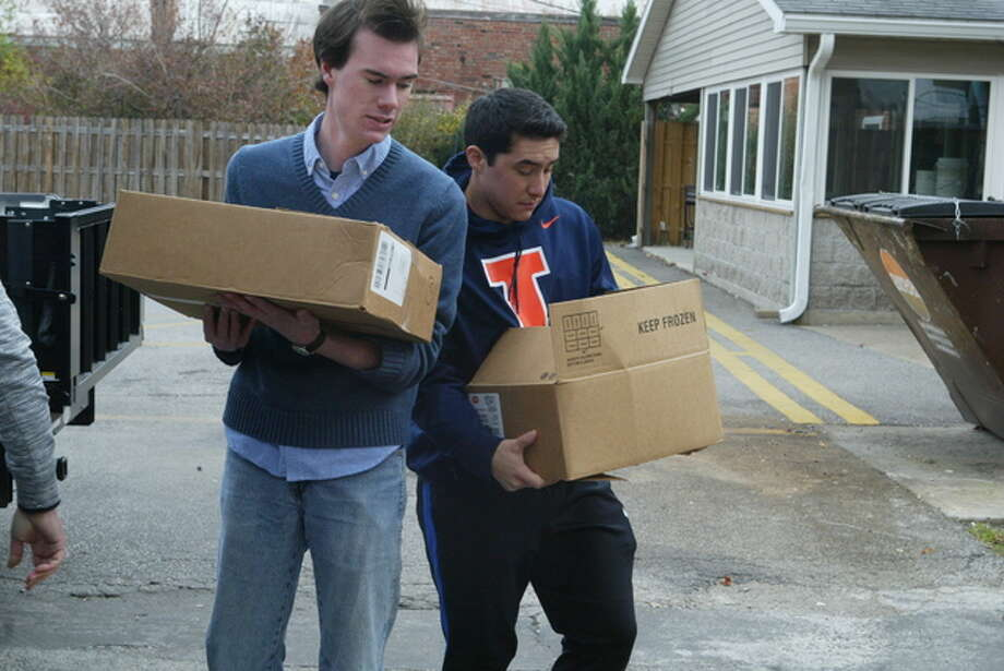 Joe Ritter of Pekin, a junior at Illinois College, and junior Roger Mies of Los Angeles help unload the 2,715 food items collected during an Illinois College campus-wide food drive for the Jacksonville Food Pantry. The goal was 2,450 items, which would amount to two items donated for every employee and student at the college.