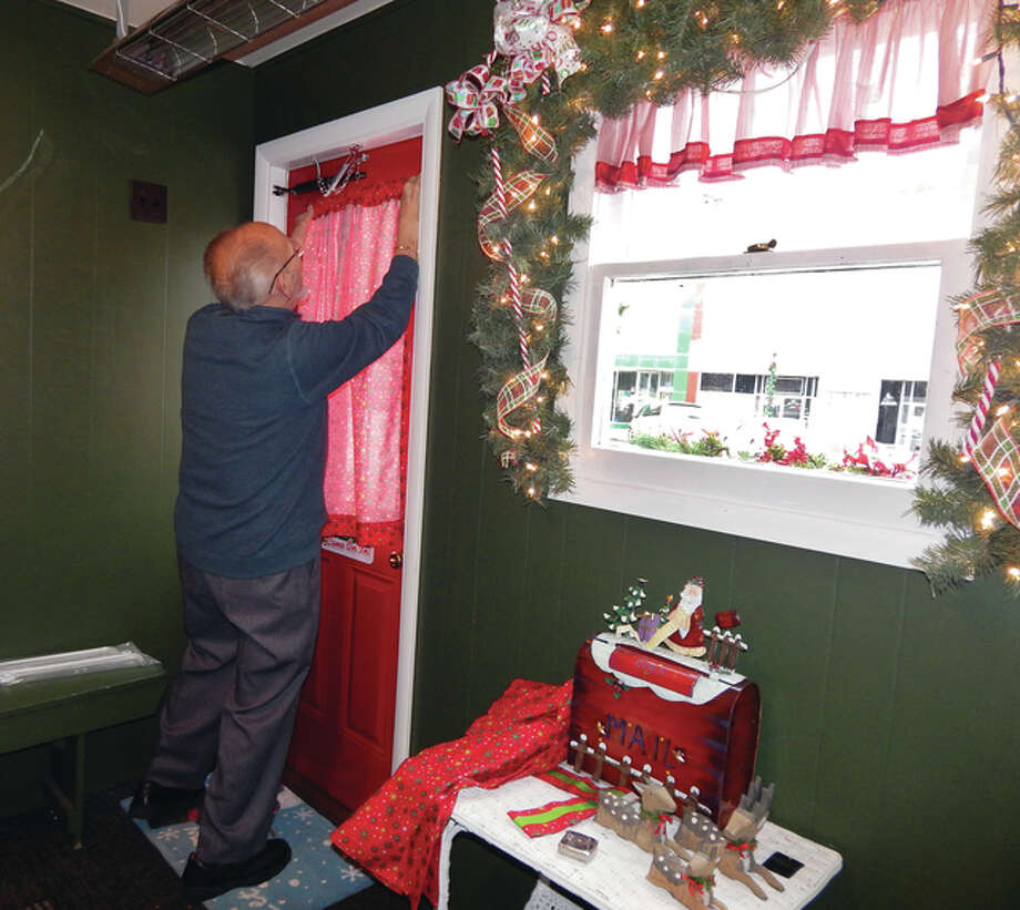 Tom Winner of Heart of Jacksonville finishes up Tuesday with last-minute decorating touches on Santa's home-away-from-home on the downtown Jacksonville square. Photo: Angela Bauer | Journal-Courier
