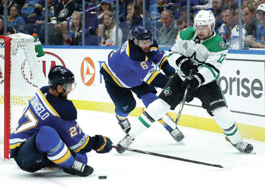 The Stars' Devin Shore (right) passes around the Blues' Joel Edmundson (middle) and Alex Pietrangelo during the third period of Saturday night's 4-2 Blues win in St. Louis.
