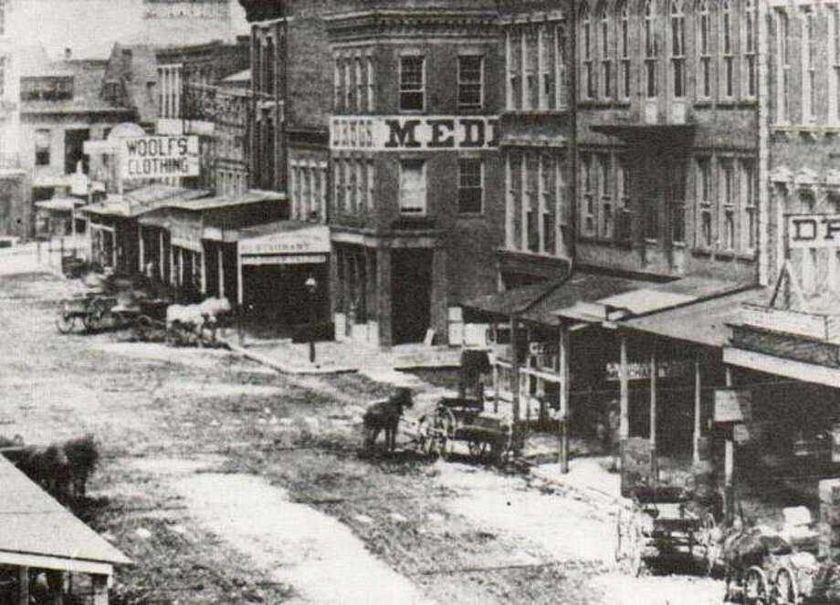 "Third Street in 1873 was ""downtown"" for Altonians. A wide variety of shops, restaurants, and banks crowded the still unpaved streets. The city did provide stepping stones to make crossing a little safer, and less muddy. Merchants; awnings extended over the board sidewalks to protect their customers. A gas street lamp stood at the corner of Third and Belle, near the Ebenezer Marsh Drug Store. The many different heights and styles of the wooden or metal roofs over the sidewalk seem to add to the confusion on the street."