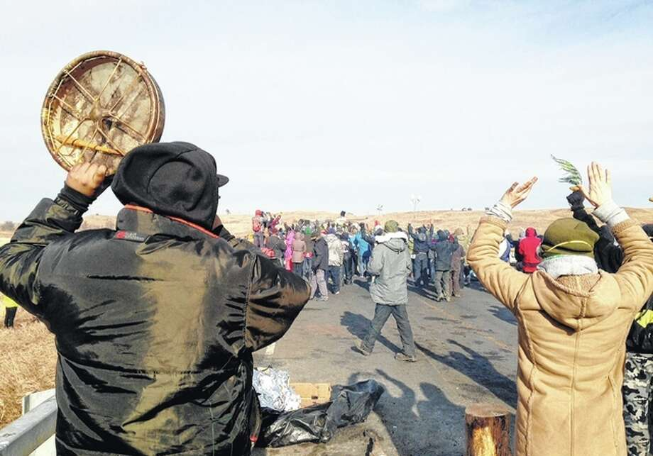 Protesters against the Dakota Access oil pipeline congregate Monday near Cannon Ball, North Dakota, on a long-closed bridge on a state highway near their camp in southern North Dakota. The bridge was the site of the latest skirmish between protesters and law officers, in which officers used tear gas, rubber bullets and pepper spray, and authorities say protesters assaulted officers with rocks and burning logs. James MacPherson | AP Photo