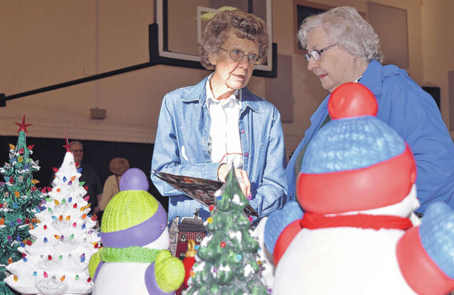 Freda Beerup (left) of Jacksonville talks with Linda Dunham of South Jacksonville on Saturday about her display of Christmas decorations at the Westfair Holiday Craft Fair in the Westfair Christian Academy gym. The event featured more than 20 vendors that sold a variety of handmade items, including Christmas ornaments, woodcrafts and florals. The vendors donated part of their proceeds toward restoration of the school's piano. Photo: Greg Olson | Journal-Courier