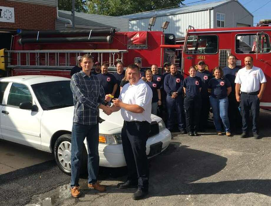 Madison County Board member James Futrell, left, presents the keys of a decommissioned police cruiser to Cottage Hills Fire Chief Steven Quartermouse after the volunteer department purchased the county-owned vehicle for $1. Photo: For The Telegraph