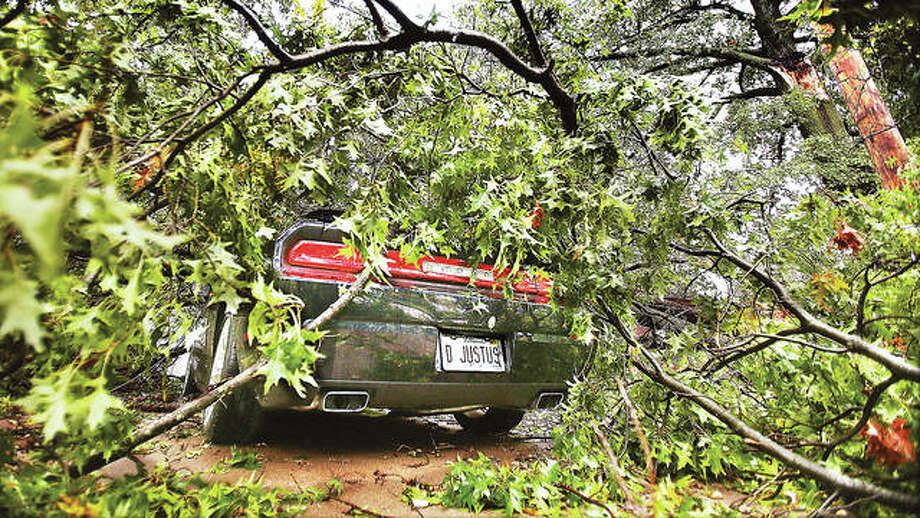 There was no justice in what happened to the 2012 Dodge Challenger of Debbie Justus in the storm late Monday night when part of a tree fell on her car in the driveway at the corner of Worden and Edwards streets in Alton. The large branch crushed part of the car's top, smashed through the windshield and rammed into her dashboard, as well as causing minor damage to the house's roof. Photo: John Badman | The Telegraph