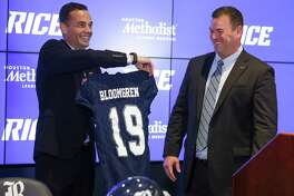 Rice University athletic director Joe Karlgaard, left, gives Mike Bloomgren, the university's new football coach, a jersey Wednesday, Dec. 6, 2017 in Houston.