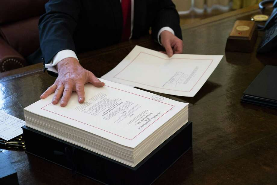 President Donald Trump signs the tax reform bill in the Oval Office of the White House in Washington, Dec. 22, 2017. Republicans are pouring government stimulus into a steadily strengthening economy, adding economic fuel at a moment when unemployment is low and wages are beginning to rise, a combination that is stoking fears of higher inflation and ballooning budget deficits. Photo: DOUG MILLS /NYT / NYTNS