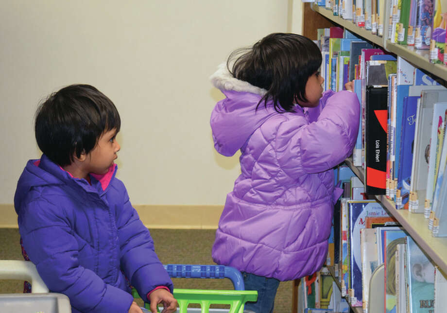 Zufra Khan (left), 2, and Asiyah Khan, 4, the daughters of Azharuddin and Minhaz Khan of Jacksonville, pick out books to read at the Jacksonville Public Library. Photo: Samantha McDaniel-Ogletree | Journal-Courier