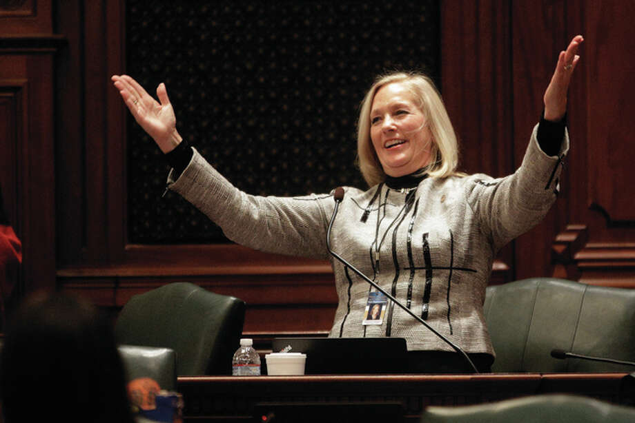 "Seth Perlman | AP Rep. Katherine Cloonen, D-Kankakee, acknowledges applauds after singing ""God Bless America"" while on the House floor during veto session at the Capitol in Springfield. Half a dozen state representatives have sued the state comptroller for holding up their paychecks during the state budget mess."