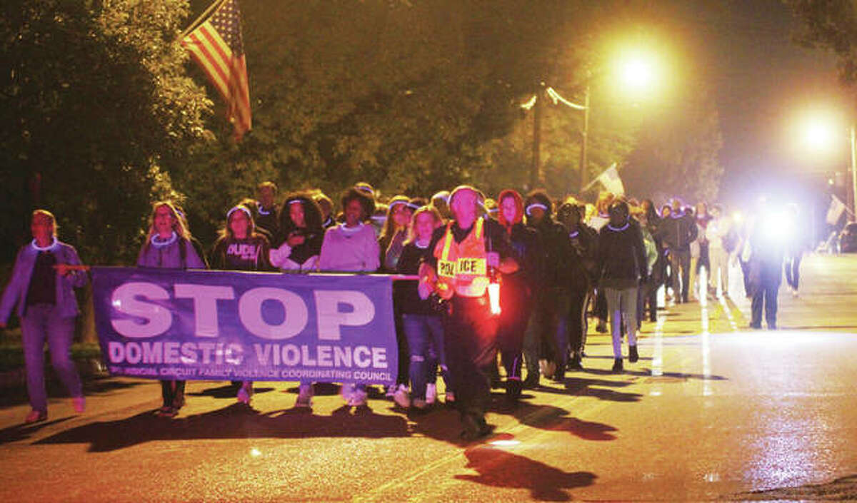 A crowd of about 100 people march along State Street toward the Alton Liberty Bank Amphitheater for the Fourth Annual Domestic Violence Awareness Walk Thursday. After meeting at the amphitheater, the crowd was bused to SS Peter and Paul Catholic Church for a program, then marched back to the Amphitheater.