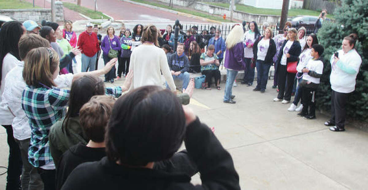 Members of the Marquette High School choir, at left, entertain the crowd at the Fourth Annual Domestic Violence Awareness Walk Thursday. After meeting at the Alton Liberty Bank Amphitheater, the crowd was bused to SS Peter & Paul Catholic Church for a program, then marched back to the Amphitheater. About 100 people participated.