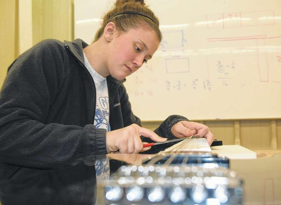 Hallie Coad, 17, of White Hall works on the fret board of the guitar she is building at North Greene High School.