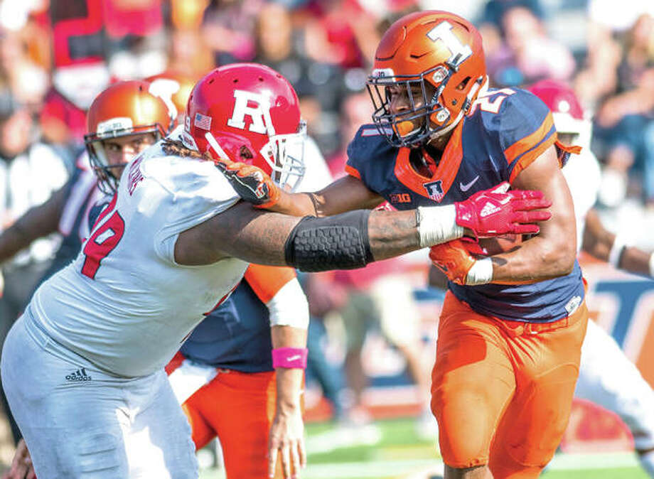 Illinois running back Ra'Von Bonner (21) is tackled by Rutgers defensive lineman Kevin Wilkins in the fourth quarter of Saturday's game in Champaign. Rutgers defeated the Illini 35-24.
