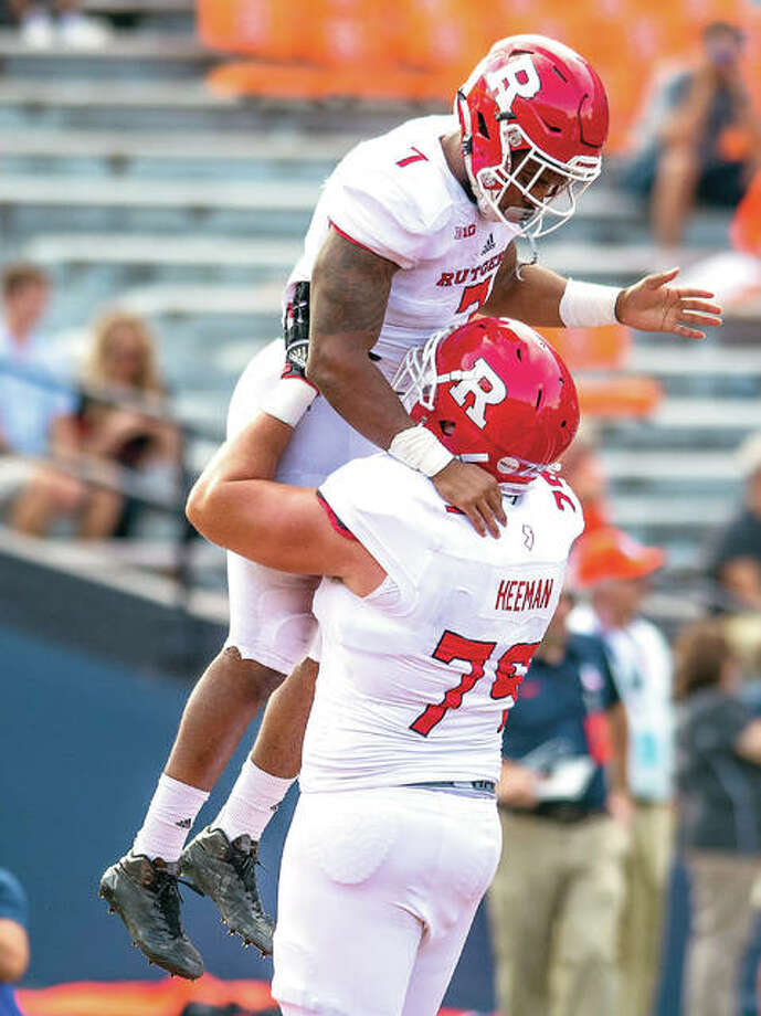 Rutgers offensive lineman Zack Heeman (79) lifts running back Robert Martin after Martin's touchdown run in the fourth quarter of Saturday's game at Illinois. Rutgers won 35-24. Photo: AP