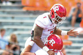 Rutgers offensive lineman Zack Heeman (79) lifts running back Robert Martin after Martin's touchdown run in the fourth quarter of Saturday's game at Illinois. Rutgers won 35-24.