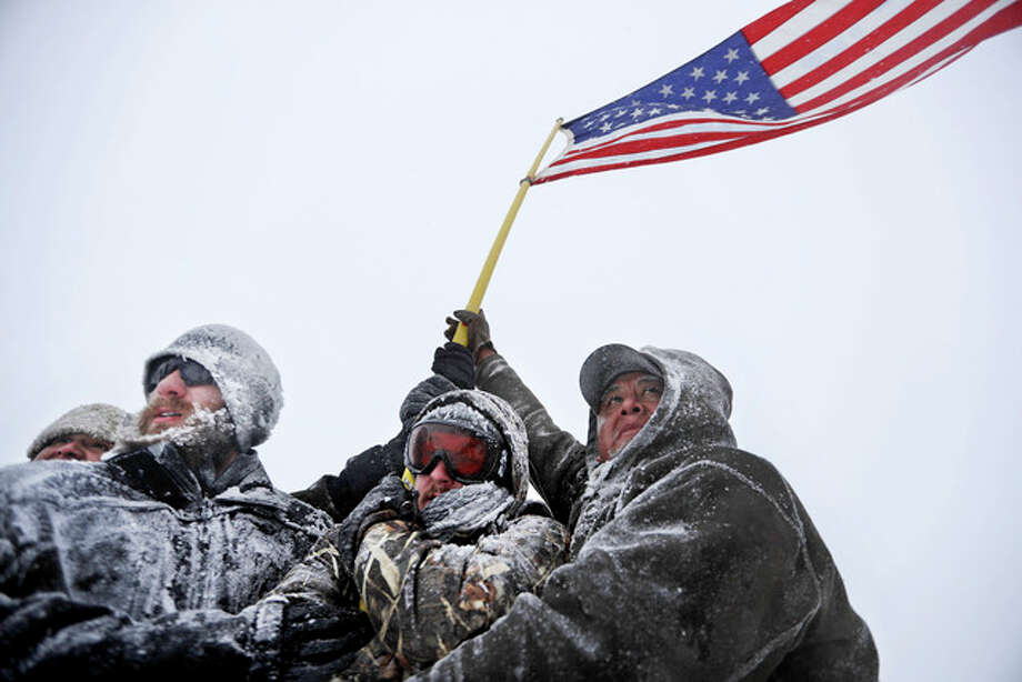 David Goldman | AP Military veterans huddle together to hold a United States flag against strong winds during a march to a closed bridge outside the Oceti Sakowin camp where people gathered Monday to protest the Dakota Access oil pipeline in Cannon Ball, North Dakota.