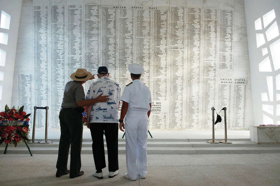 Lauren Bruner, one of five remaining survivors of the USS Arizona from the Dec. 7, 1941, Japanese attack of Pearl Harbor, is joined by Capt. Jeffry W. James (right), then the commander of Joint Base Pearl Harbor-Hickam, and Daniel Martinez, chief historian for the National Park Service, in 2013 as they look at the Arizona Memorial's Shrine Wall with names of every man aboard the ship when it was attacked. More than 2,300 servicemen died in the Japanese attack that plunged the United States into World War II. Nearly half of those killed were on the Arizona, most still entombed in the wreckage.