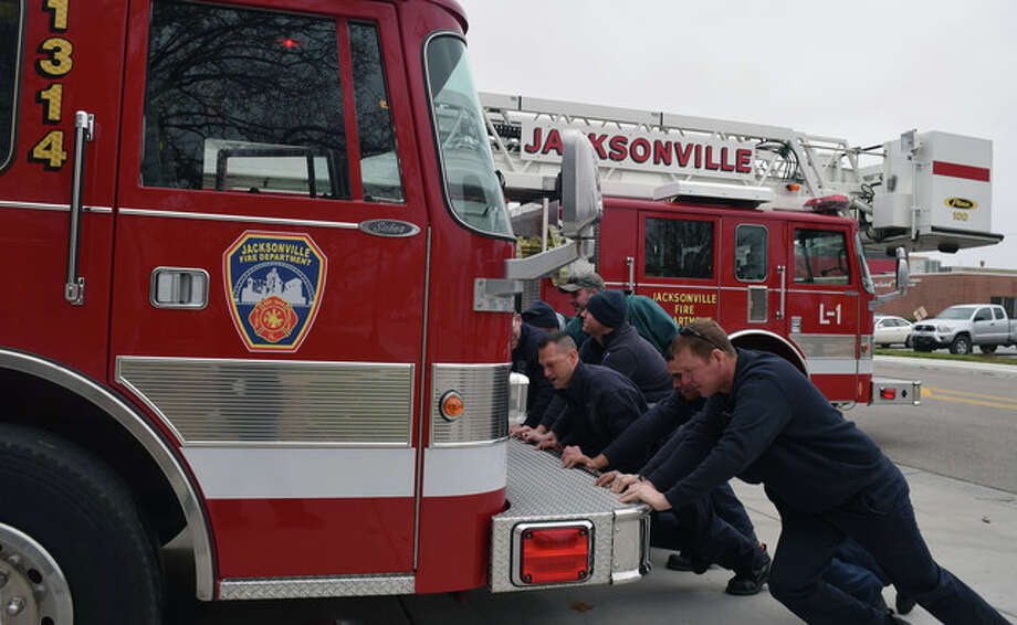 Jacksonville Fire Department members push a new truck into the station Tuesday. There is a tradition of backing new apparatus into the station when it is ready for use. The tradition comes from when fire engines were horse-drawn and firefighters would have to unhook the horses and push the truck back inside after every use. Photo: Samantha McDaniel-Ogletree | Journal-Courier