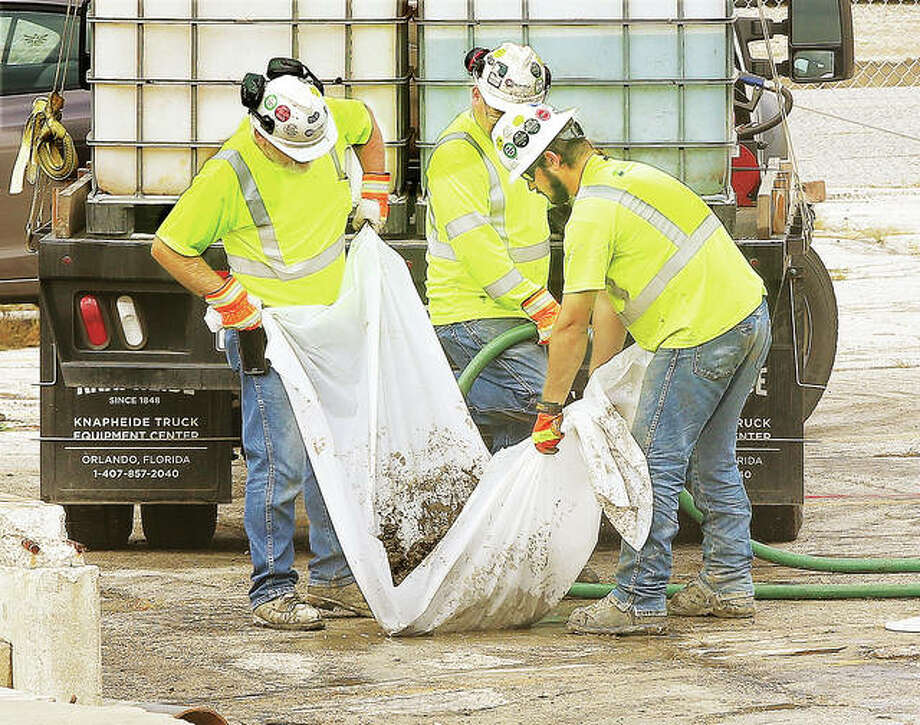 Earlier this month, employees of Cascade Drilling are shown using a sheet of plastic as a makeshift mixer for a concrete or slurry patch to plug one of the holes they drilled in the parking lot of the old, Downtown U.S. Post Office site on Belle Street in Alton. Testing continues, but no remediation work has started yet on groundwater and soil contamination. Photo: John Badman | The Telegraph