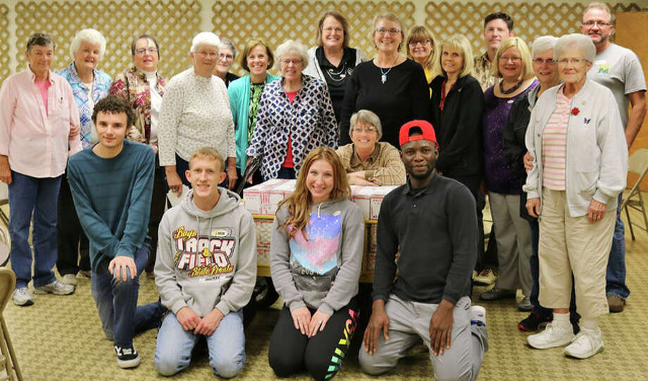 Members of the Jacksonville Rotary Club, Illinois College Rotaract Club and Franklin Waverly Military Support Group take a break after packing and sealing 83 holiday care boxes for shipment to military service members.