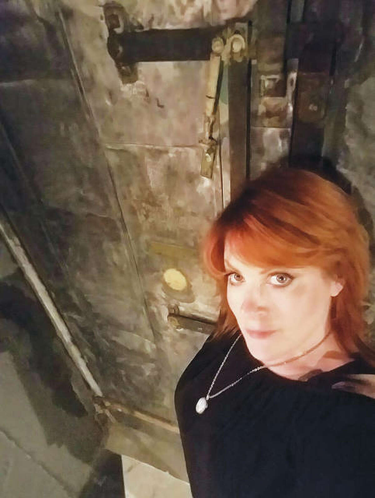 Psychic medium Missy Nichols, who owns Taboo Paranormal, which conducts Milton Schoolhouse tours, is pictured standing in front of Milton's boiler room door. The boiler room is one of the building's areas included on the tours that meet at Maeva's Coffee, inside the building at 1320 Milton Road, Alton.