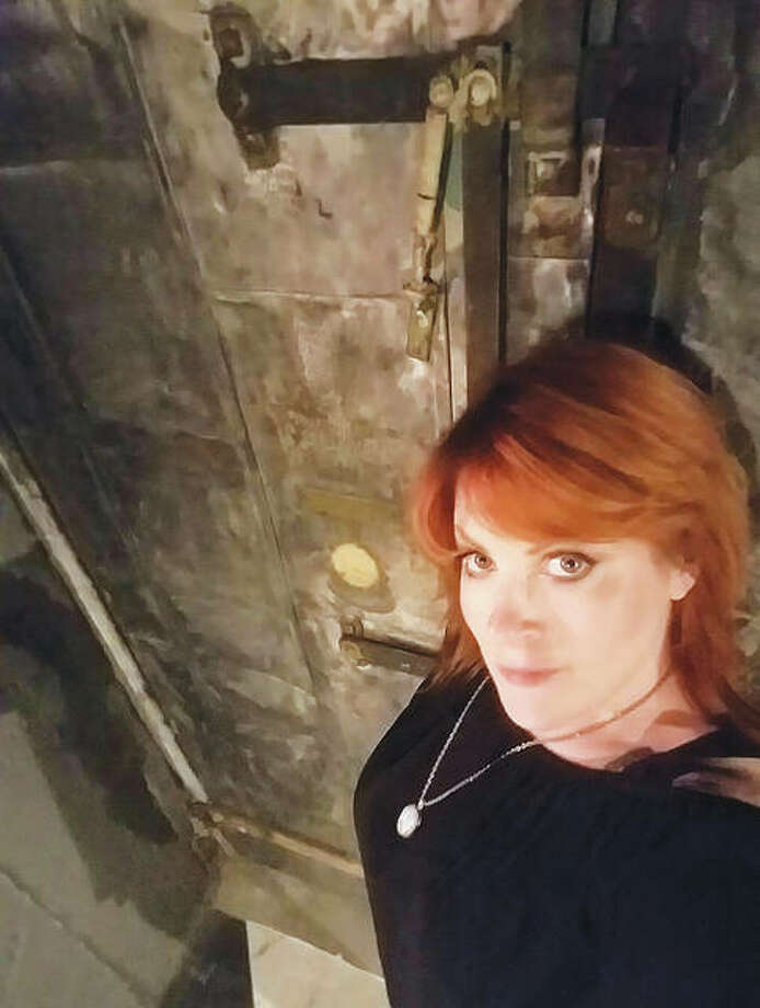 Psychic medium Missy Nichols, who owns Taboo Paranormal, which conducts Milton Schoolhouse tours, is pictured standing in front of Milton's boiler room door. The boiler room is one of the building's areas included on the tours that meet at Maeva's Coffee, inside the building at 1320 Milton Road, Alton. Photo: For The Telegraph