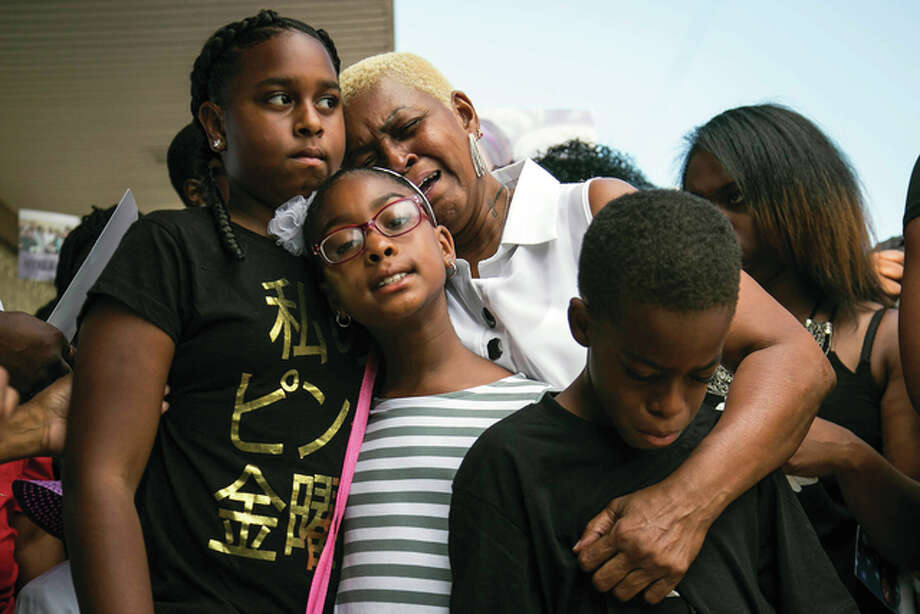 Ashlee Rezin | Chicago Sun-Times (AP) Diann Aldridge hugs her grandchildren, Summer (left), Sincere (right) and Shavae during a vigil in August for their mother, Nykea Aldridge, in Chicago. Aldridge, a 32-year-old mother of four, and the cousin of NBA star Dwyane Wade, was shot and killed by repeat offenders while pushing her baby in a stroller. Illinois legislators are facing mounting pressure to lengthen sentences on repeat criminals who return to the streets and contribute to Chicago's violence after serving only a portion of their prison terms.