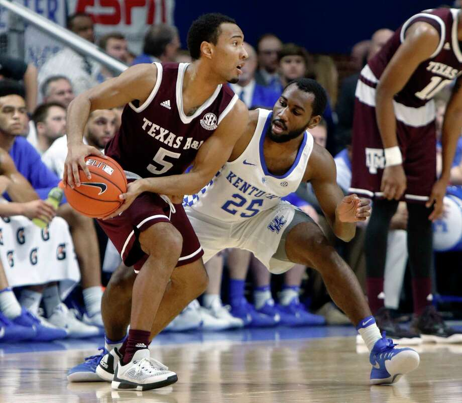 Texas A&M's JC Hampton (5) looks for an opening as Kentucky's Dominique Hawkins defends during the first half of an NCAA college basketball game, Tuesday, Jan. 3, 2017, in Lexington, Ky. Kentucky won 100-58. (AP Photo/James Crisp) Photo: James Crisp, Associated Press / FR6426 AP
