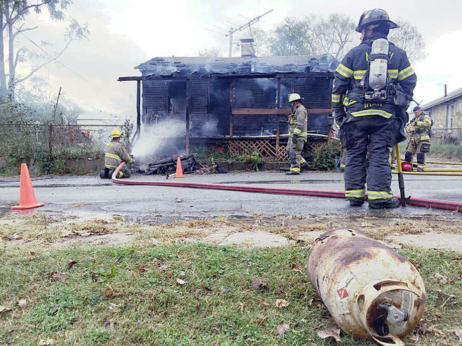 A singed propane tank — which, ironically, may not have been the source of the fire — rests in the grass across the street from 408 George St. in East Alton Friday afternoon, as firefighters continue to spray water on the smoking house. East Alton firefighters were called to respond to the structure fire at 4 p.m. Friday, and despite a quick response, the fire spread quickly through the residence. Occupants, none of whom were injured, say the fire started on the front porch, where they had been grilling just minutes earlier. Photo: Nathan Grimm   The Telegraph