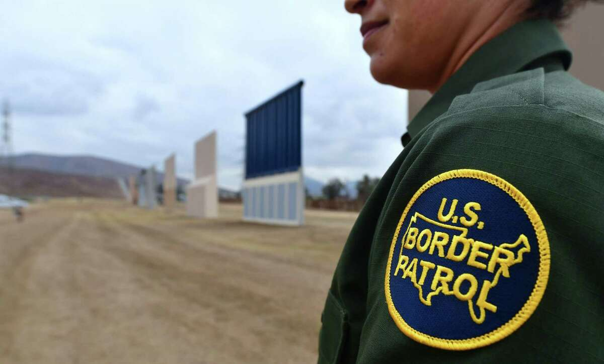 """(FILES) In this file photo taken on November 1, 2017 US Border Patrol officer Tekae Michael stands near prototypes of US President Donald Trump's proposed border wall in San Diego, California. A border patrol agent whose mysterious death prompted President Donald Trump to renew his call for a wall along the US-Mexico border appears to have died as the result of an accident, according to an FBI probe. An FBI investigation into the November 2017 death of agent Rogelio Martinez has not found any evidence of foul play.""""To date none of the more than 650 interviews completed, locations searched, or evidence collected and analyzed have produced evidence that would support the existence of a scuffle, altercation, or attack,"""" the FBI said in a statement on February 7, 2018. / AFP PHOTO / FREDERIC J. BROWNFREDERIC J. BROWN/AFP/Getty Images"""