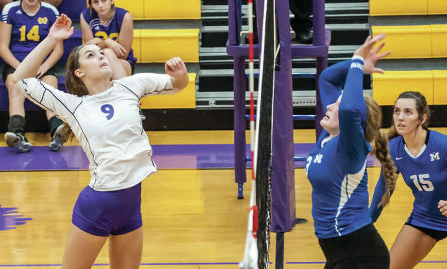 CM's Hannah Schmidt (left) goes up for an attack while Marquette Catholic's Regina Guehlstorf goes up for a block and Jenna Zacha (15) watches the play during a match at the Roxana Tournament on Aug. 30. CM was back at Roxana's Milazzo Gym on Monday and saw its season ended with a Class 3A regional loss, while Marquette was in Dupo for a win that sent the Explorers to Tuesday's semifinals. Photo: Nathan Woodside / For The Telegraph