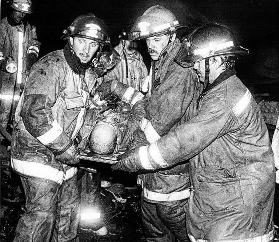 In this photo from the day of the fatal fire, Alton firefighters rush an injured Capt. Dan Walter to a waiting ambulance after he suffered a crushed ankle when the building collapsed. Walter was one of three other firefighters injured in the fire, which killed two members of the department. Photo: John Badman | The Telegraph