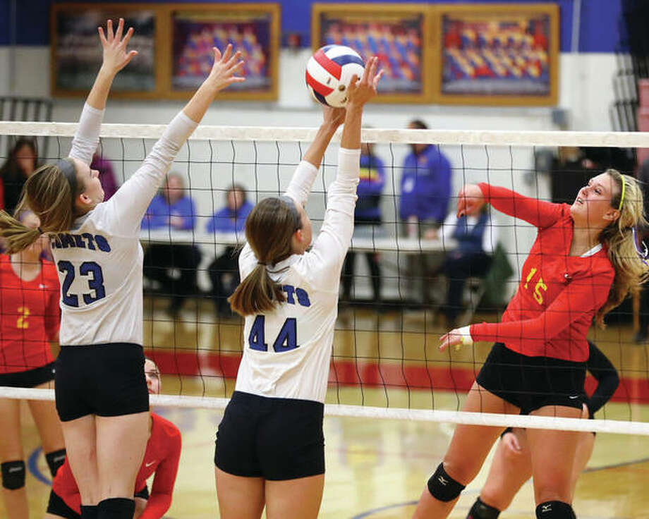 Roxana's Braeden Lackey (right) shoots an attack past the block of Greenville's Kalie Meadows (23) and Hannah Williams (44) during Tuesday's semifinal match in the Roxana Class 3A Regional at Larry Milazzo Gymnasium in Roxana. Photo: Billy Hurst / For The Telegraph