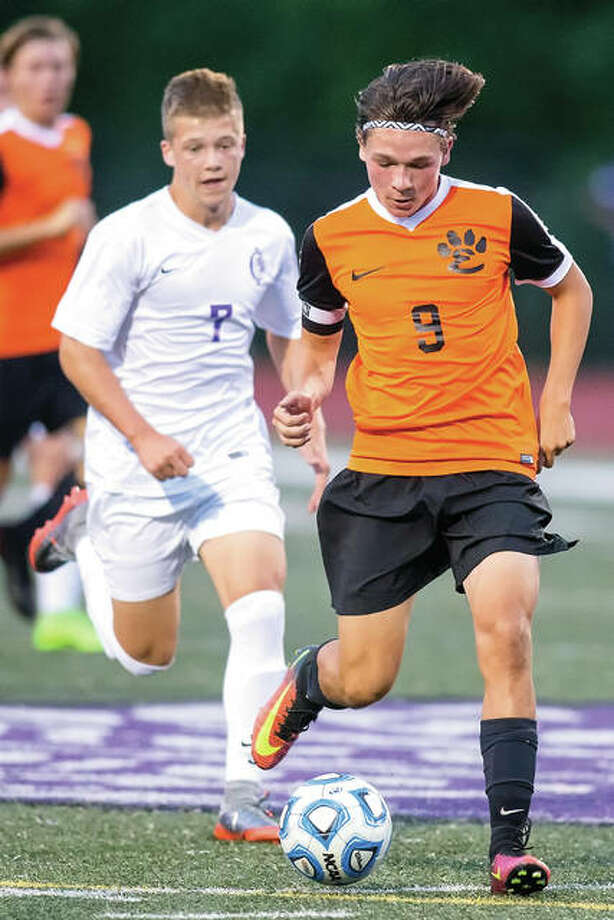Edwardsville's Kyle Wright (9) is pursued by Collinsville's Luke Liljegren during a 3-0 Tiger win Sept. 12 in Collinsville. The teams met again Tuesday in a Class 3A sectional semifinal in O'Fallon. Photo: Scott Kane / For The Telegraph