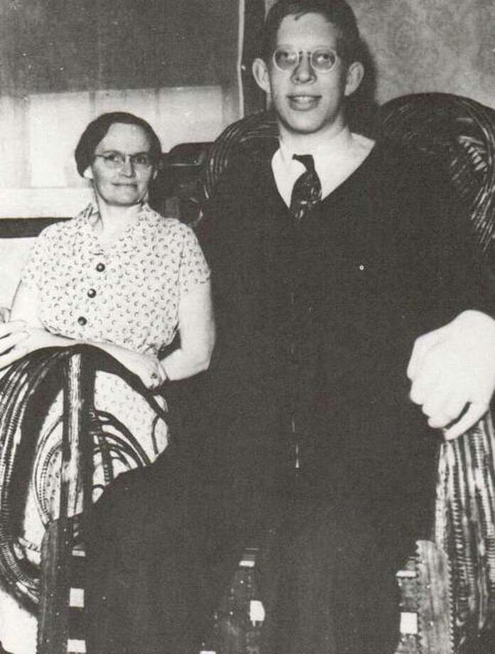 Robert Wadlow was very fond of his mother, Addie. Here he is shown in his specially made woven chair at home. His parents and brothers and sisters were of normal size.