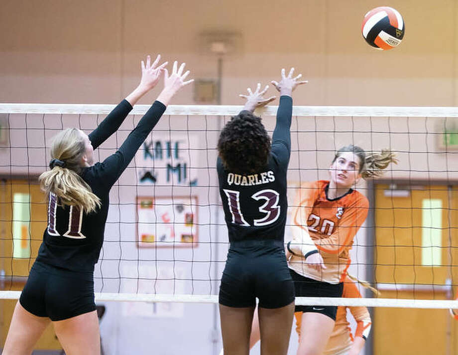 Edwardsville's Kate Martin (right) hits past the double block put up by Belleville West's Katherine Koch (11) and Nisha Quarles (13) during the Tigers' Southwestern Conference win Oct. 17 in Edwardsville. Martin had 11 kills in Tuesday's semifinal win over Chatham Glenwood at the Quincy Class 4A Regional. Photo: Scott Kane / For The Telegraph