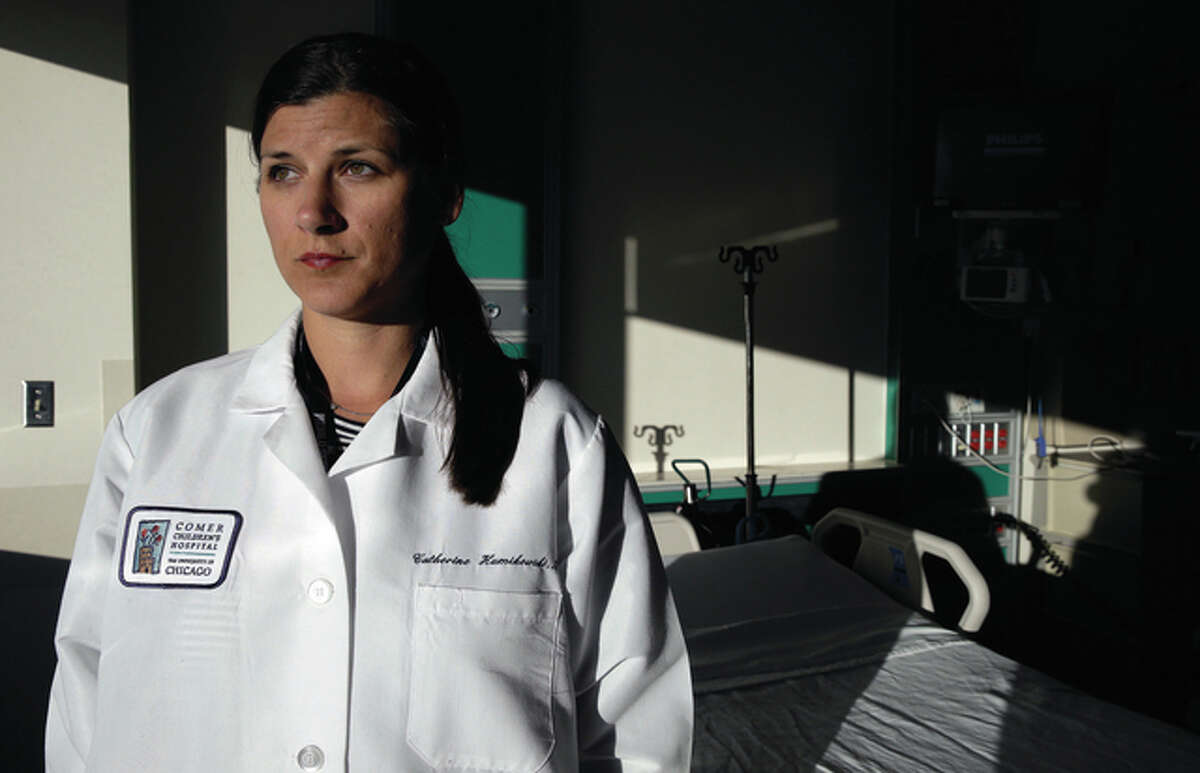 Kiichiro Sato | AP Catherine Humikowski, medical director of the pediatric ICU at the University of Chicago Comer Children's Hospital, has seen the grievous damage bullets do when they rip into young brains and bodies. She says it's physically exhausting and has transformed her life outside of work.