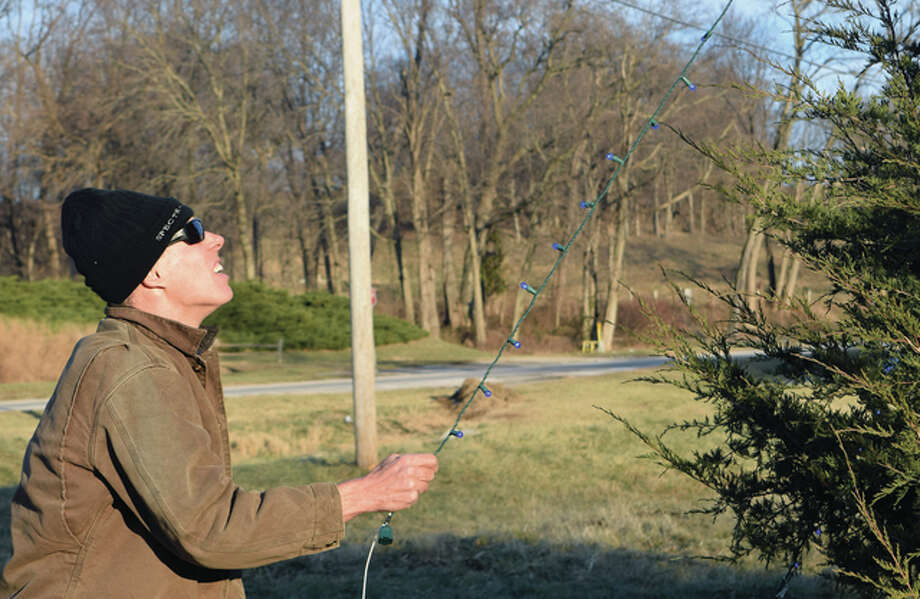 Jonn Herzberger stretches a string of lights that was hung on a tree along Route 125 in Bluff Springs. Photo: Samantha McDaniel-Ogletree | Journal-Courier