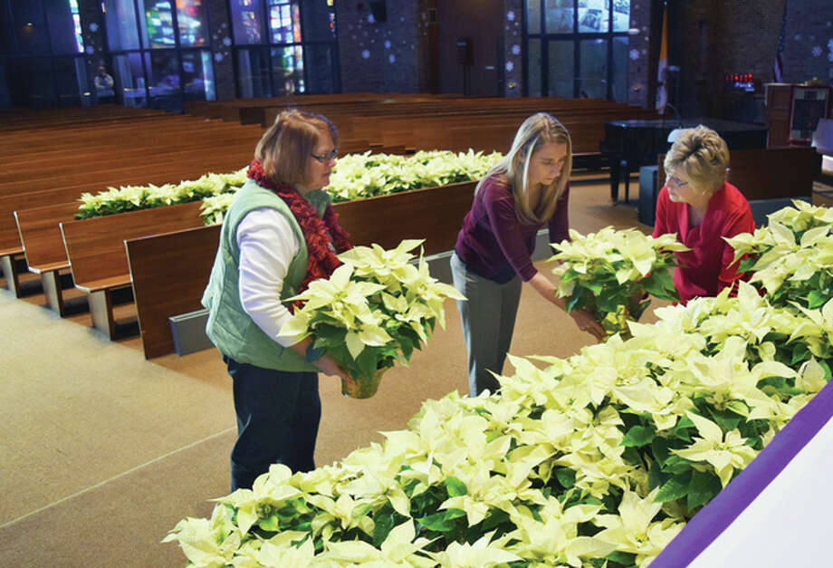 Our Saviour Parish members Betty Gibson (from left), Fritzie Wagner and Rose Marie Beeley place poinsettias in front of the altar at the Church of Our Saviour on Thursday in preparation for this weekend's Christmas Masses. Photo: Greg Olson | Journal-Courier