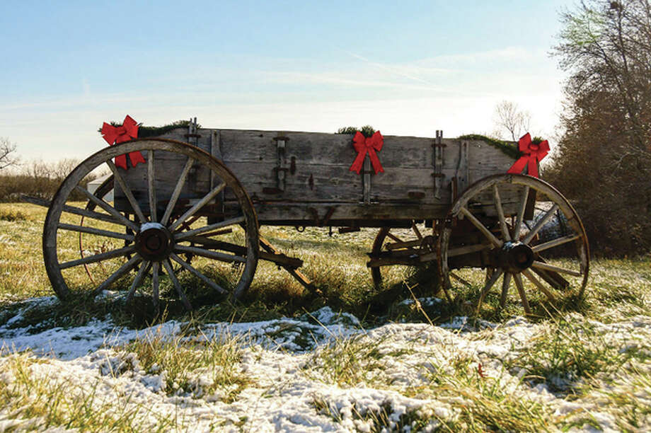 An old wagon sits in a field, adorned for Christmas.