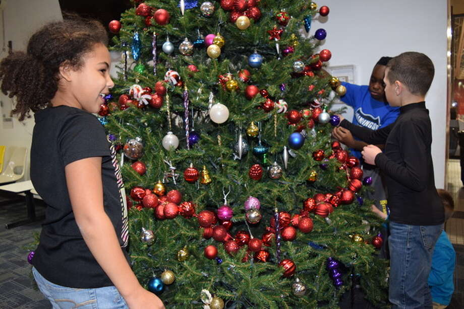 Kendall Graham (from left), 9, Emmanuel Moore, 10, and Avery Stewart, 9, replace ornaments on a Christmas tree Friday at the Bob Freesen YMCA during the Y's after-school program. Photo: Nick Draper | Journal-Courier