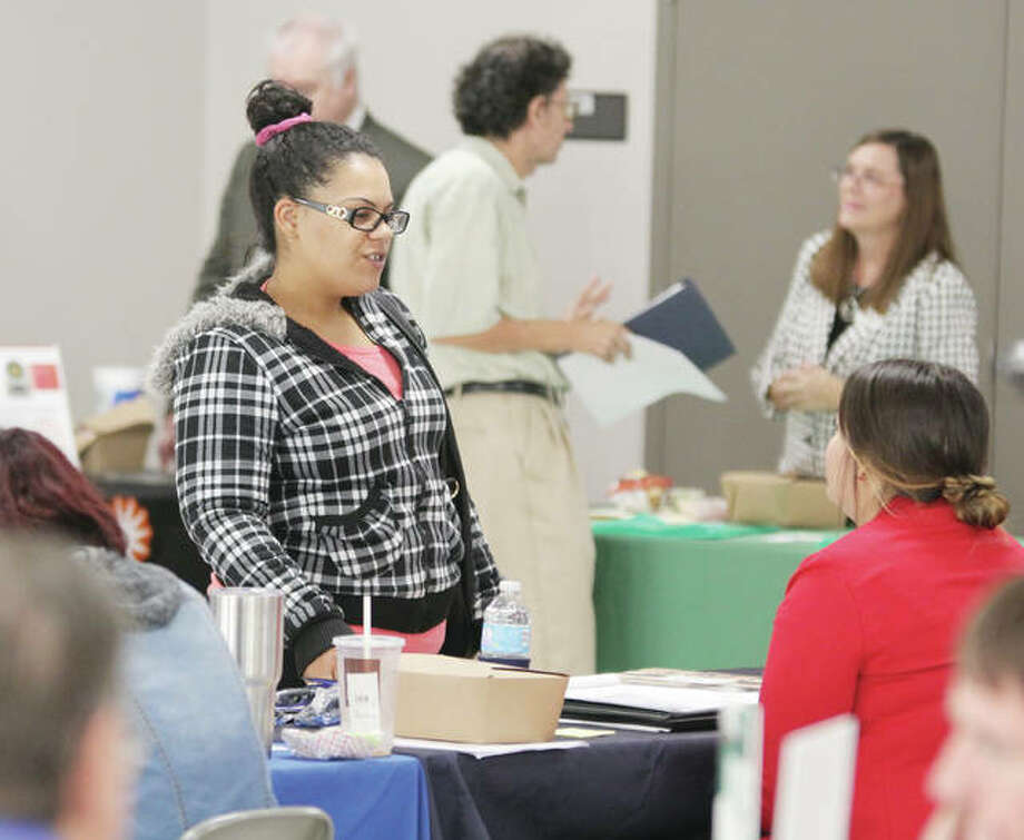 An Alton resident talks to representatives of local businesses, schools and educational agencies during a job fair in Alton. Photo: Scott Cousins | The Telegraph