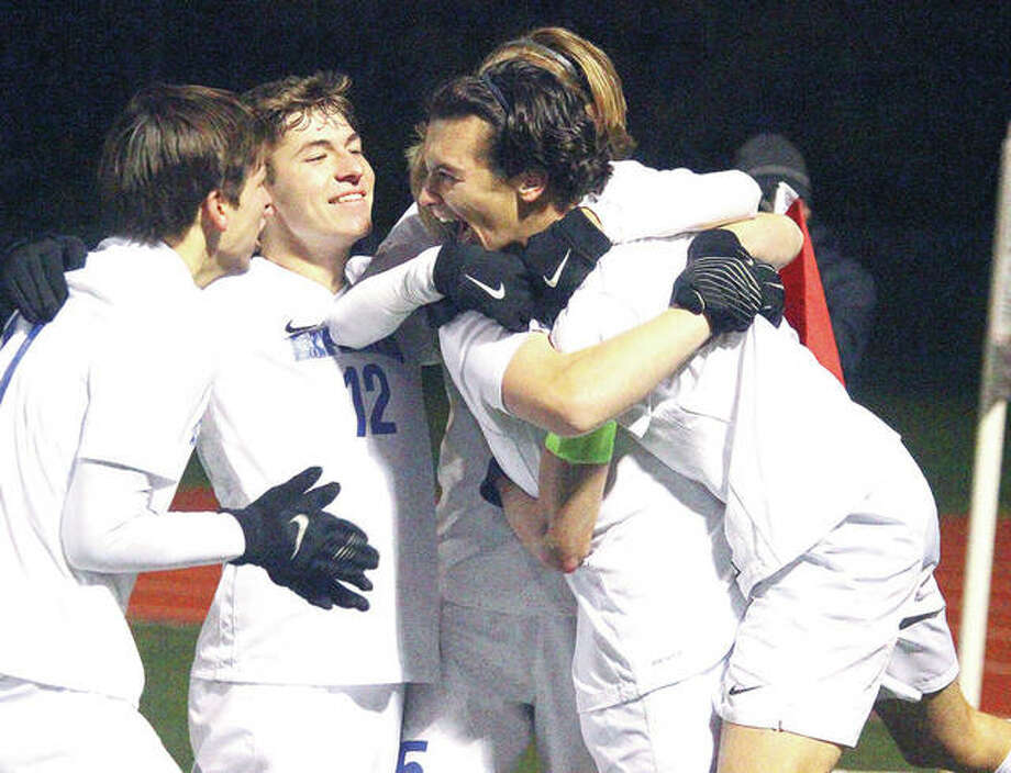 Marquette's Noah Fahnestock celebrates with teammates Isaac Hendrickson and Nick LaFata after scoring a penalty kick in the second half of Saturday night's Class 1A state title game. Photo: Clark Brooks, PhotoNews Media | For The Telegraph