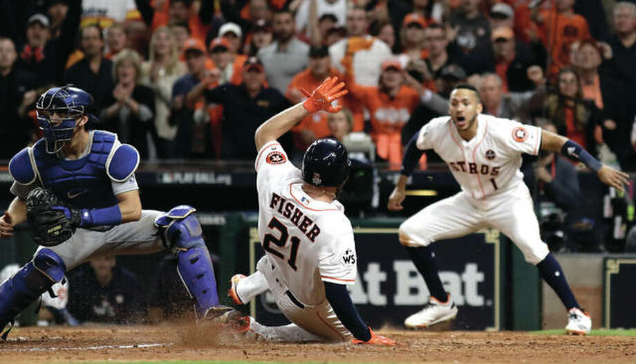 The Astros' Derek Fisher (center) scores during the 10th inning of Game 5 of the World Series against the Los Angeles Dodgers on Monday night in Houston. The Astros lead the series 3-2. Photo: Associated Press